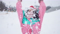 Cheerful slim young woman in New Year hat tossing white snow in slow motion outdoors smiling. Portrait of happy carefree Caucasian female tourist enjoying winter fun at resort. 76041333
