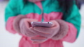 Close-up of smartphone in female hands outdoors. Unrecognizable woman in ski suit and pink mittens messaging online resting at winter resort. Wireless communication and winter vacations. 76041334