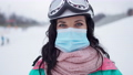 Close-up portrait of young Caucasian woman in coronavirus face mask and ski suit looking at camera posing outdoors. Headshot of female tourist resting at snowy winter resort on Covid-19 pandemic. 76041335