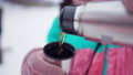 Close-up of female hands in pink mittens pouring tea from thermos outdoors. Unrecognizable young female skier with hot drink at winter ski resort. Cold weather and vacations concept. 76041336