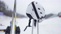 Ski helmet on poles with skis and blurred winter resort at background. Skiing equipment outdoors. 76041337