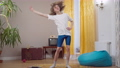Wide shot portrait of skinny young retro man exercising indoors in 1980s or 1990s. Motivated Caucasian guy in vintage house training at home. Sport and healthy lifestyle 76074123