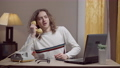 Portrait of young retro man picking up phone and talking smiling. Middle shot of Caucasian guy with long curly hair sitting at table in 80s 90s living room with vintage telephone and laptop 76074124