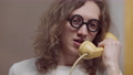 Headshot of furious young man in vintage eyeglasses yelling in retro telephone handset and hanging up. Portrait of angry Caucasian curly-haired stressed guy indoors 76074125