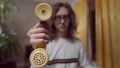 Close-up of yellow vintage telephone handset in male hand with blurred 1980s 1990s nerd at background. Young Caucasian man holding retro outdated old-fashioned phone posing indoors at home 76074126