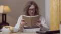 Portrait of absorbed nerd in retro eyeglasses reading book at home. Engrossed interested Caucasian young man enjoying literature in 1980s 1990s indoors. Intelligence and lifestyle 76074128