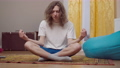 Young 80s styled man meditating in lotus pose at home. Portrait of relaxed Caucasian guy practicing yoga exercising indoors in 90s. Meditation and sport in retro style 76074129