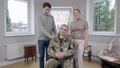 Caucasian woman and man holding hands on shoulders of disabled military soldier in wheelchair. Portrait of wife and son posing with paraplegic middle aged veteran at home indoors. 76090904