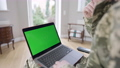 Laptop with green screen on knees of unrecognizable Caucasian military man indoors. Adult soldier or veteran surfing Internet or messaging online at home. Modern technologies, chromakey. 76090906