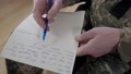 Close-up of male Caucasian middle aged hand writing letter with pen on paper. Unrecognizable military man sitting indoors handwriting. Army lifestyle concept. 76090907