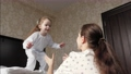 Happy daughter jumps out of bed to her mother in her arms and hugs her. Mother plays with her baby in morning. Family is having fun at home. Active family vacation at home. Happy healthy childhood 76092150