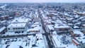 Drone flies over small snowcovered town at winter evening, 76094161