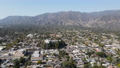 Aerial view above Pasadena neighborhood with mountain on the background. California 76099786