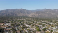 Aerial view above Pasadena neighborhood with mountain on the background. California 76099789