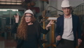 Happy heavy industry business engineering and manager in hardhats dancing funny together indoors welding manufacturing industrial factory after success project, slow motion 76103147