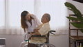 Female nurse doctor wear white uniform cardiologist examining patient senior or elderly old man during sit on wheelchair listening checking heartbeat using stethoscope at home, Health visitor concept 76103151