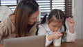 Asian family young mother and her little daughter smiling using laptop computer together for learn online and eating instant noodles at home, Child eats noodles while doing homework 76103152