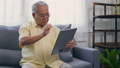 Asian elderly patient video call by digital tablet to doctor for inquire about which bottle of medication pills should be taken in living room at home,  Senior old man technology online healthcare 76103154