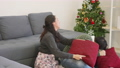 Happy Asian beautiful young family couple husband and wife smile and laugh enjoying funny fighting with pillows in living room with winter day at home. slow motion 76103156