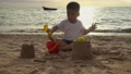 Happy fun Asian child cute little boy playing sand with toy sand tools at a tropical sea beach in holiday summer on sunset time, tourist trip concept 76103162