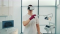 Close-up of multiracial doctor in virtual reality glasses speaking something and gesturing in modern sports lab. 76109333