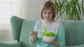Happy elderly woman eats a bowl of vegetable salad 76112469