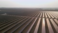 Aerial drone view into large solar panels at a solar farm at early spring sunset. Solar cell power plants. footage video 4k. 76124433