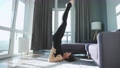 Young caucasian woman in black jumpsuit doing yoga at home to develop flexibility and balance. 76127519