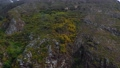 Aerial view of a rocky mountain surface covered with sparse vegetation. A power line has been installed along the ridge. Tenerife, Canary Islands, Spain 76127522