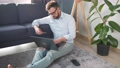 Man with glasses sitting on the floor and makes an online purchase using a credit card and laptop. Online shopping, lifestyle technology 76127983