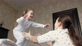 Happy daughter jumps out of bed to her mother in her arms and hugs her. Mother plays with her baby in morning. Family is having fun at home. Active family vacation at home. Happy healthy childhood 76142570
