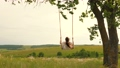 A young girl in dress swinging on swing in evening park. Wooden swing with swinging free, happy woman outdoors. Swing on a swing, dreams of flying. Travel in spring summer in nature. Healthy lifestyle 76142571