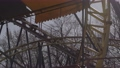 An abandoned, rust-covered roller coaster ride in an abandoned amusement park. 76147449