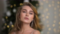 Portrait of a beautiful young woman in a festive silver evening dress with open shoulders. Christmas Eve and New Year's Eve. Christmas tree with garlands and lights in the background. 76152088