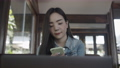 Smiling young Asian woman using smartphone at coffee shop. 76154785