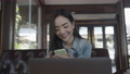 Smiling young Asian woman using smartphone at coffee shop. 76154786