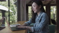 Young Asian woman freelance is working with laptop at coffee shop.  76154791