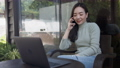 Asian woman freelance talking on mobile phone while typing on laptop in coffee shop. 76154799