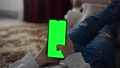 A teenager looks at information on a smartphone. The screen is a green background. 76156300