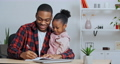 Afro american man father teacher holding little girl daughter teaching child to write playing talking to kid helping with homework, dad and toddler giving five making gesture teamwork cooperation 76161725