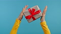 Hands of woman with gift box and bow. She is happy and flattered by attention. Present on blue 76165047
