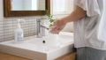 Woman washing hands in the bathroom 76168564