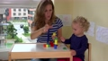 mother with little child build towers colors log in room. FullHD 76171666