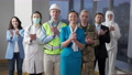 Confident positive people of different professions clapping and smiling looking at camera. Group of cheerful Caucasian men and women posing indoors in professional uniform. Confidence and occupations. 76173521