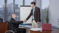 Senior paraplegic man in wheelchair and positive young male employee shaking hands in office at whiteboard with graph. Side view of confident Caucasian business partners making deal indoors. 76173522