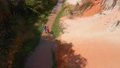 Aerial slowmotion shot. A woman and her son walk along a red canyon or Fairy stream at the border of desert in the Mui Ne village in southern Vietnam 76203388