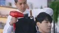 Young hairdresser using hairdryer on client 76216470