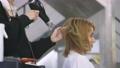 Hairdresser using hairdryer on client hair 76216511