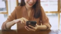Hands of young woman using smartphone in cafe 76216519