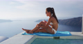Sunscreen suntan bikini woman applying sunscreen spf lotion on leg on vacation 76223767